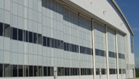 Translucent polycarbonate glazing used on an aircraft hangar door with glass windows.